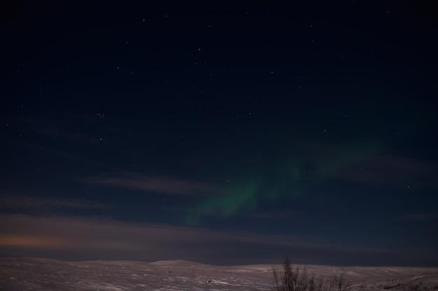 Lumière du nord sur le champ silencieux avant le lever du soleil.