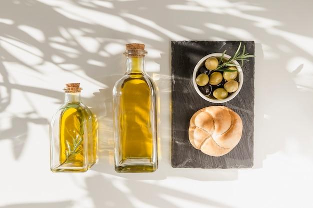 Lumière du soleil sur les bouteilles d'huile d'olive avec pain et olives sur la plaque d'ardoise