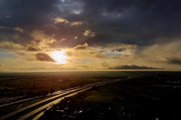 La lumière du soleil panoramique avec un ciel dramatique sur un lever de soleil sombre et vif sur l'autoroute cloudover
