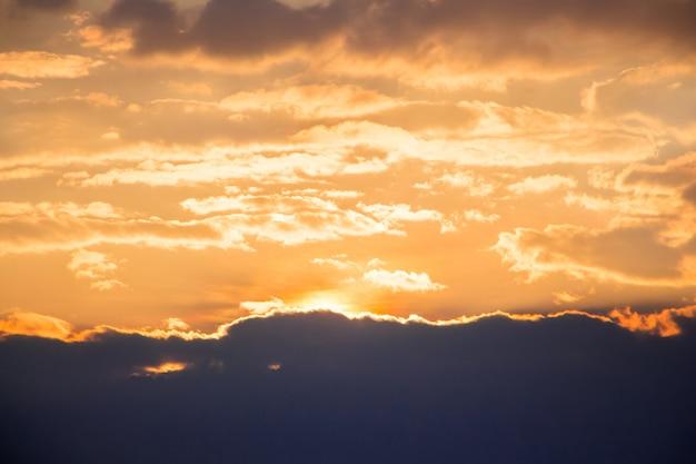 La lumière du soleil pénètre à travers les nuages sombres dans le ciel jaune, le ciel au coucher du soleil