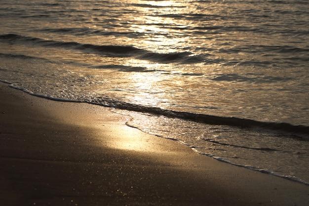 La lumière du soleil se reflète sur l'eau de mer des vagues au lever du soleil sur la côte,