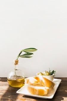 Lumière du soleil tombant sur une tranche de pain avec des olives dans le bol sur le bureau en bois