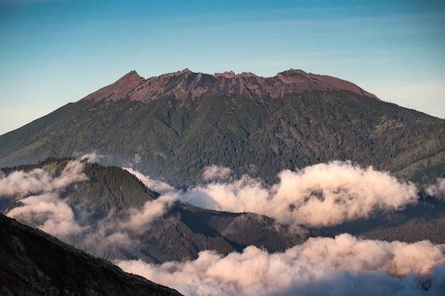 La lumière du soleil sur le volcan de pointe avec du brouillard le matin à kawah ijen