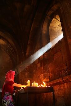 La lumière naturelle du soleil brille dans une église médiévale d'une femme allumant des bougies