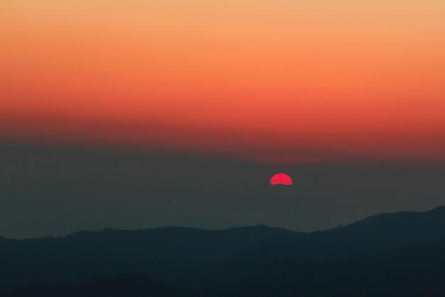 Lumière orange du coucher de soleil sur le sommet.