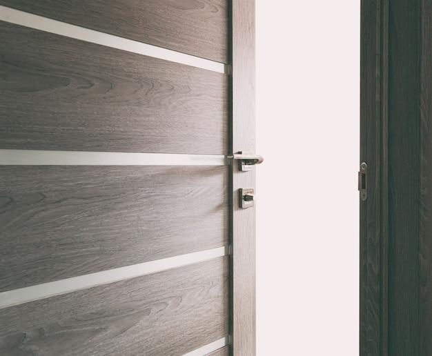 La lumière révélant à travers la porte en bois entrouverte de la maison