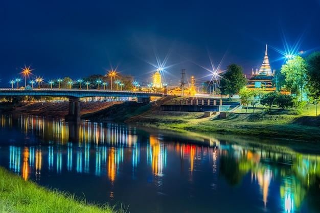 Lumière sur la rivière nan sur le pont naresuan et chedi de wat ratchaburana et prang wat phra si rattana mahathat également familièrement à la rivière nan et au parc de nuit à phitsanulok, en thaïlande.
