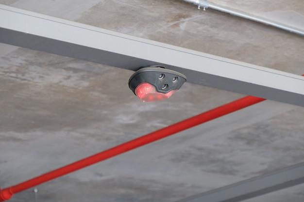 La lumière rouge de la lampe électronique pour indicateur indique l'emplacement indisponible dans le parking du centre commercial, vue de face avec l'espace de copie.