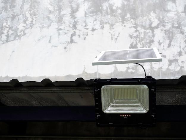 Lumière solaire montée sur un toit sur fond de bâtiment en béton avec espace de copie. lampadaire avec panneau solaire.