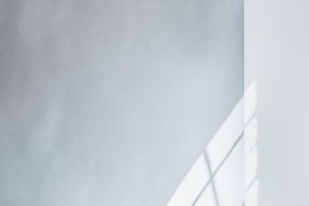 Lumière à travers la fenêtre sur un fond de mur blanc
