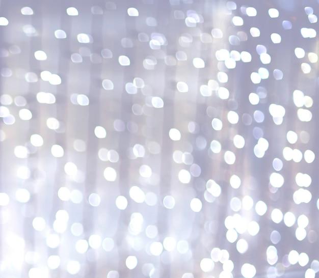 Lumières de bokeh argentées et blanches défocalisées. abstrait. photo avec un espace pour le texte