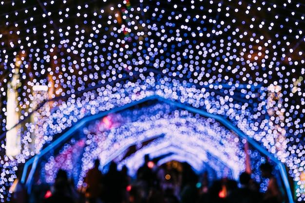 Lumières bokeh avec des gens flou en arrière-plan. festival de noël