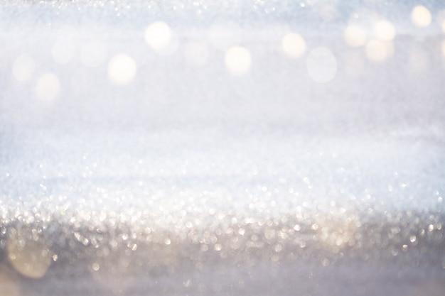 Lumières de bokeh de paillettes argent abstraites avec fond clair et doux.