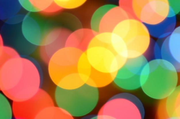 Lumières colorées festives floues sur noir utiles comme arrière-plan