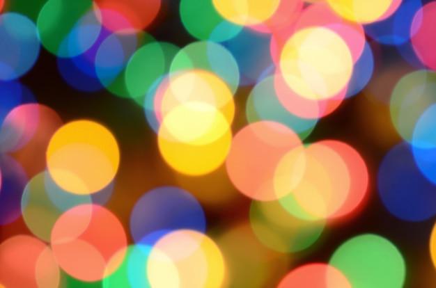 Lumières colorées festives floues sur noir utiles comme arrière-plan.
