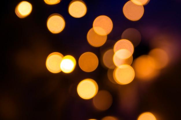 Lumières dorées floues dans la nuit. fond de vacances fête glamour