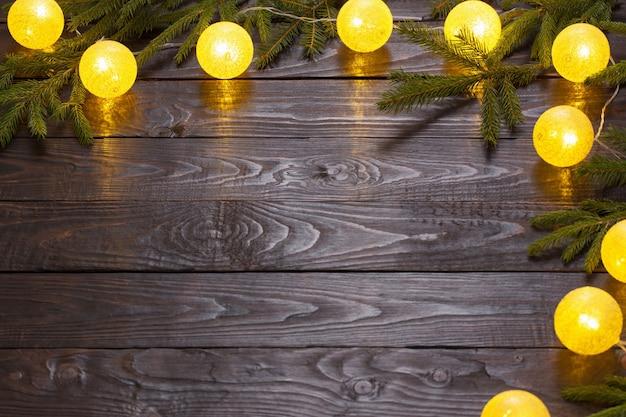 Lumières de noël avec des branches de sapin sur fond de bois foncé