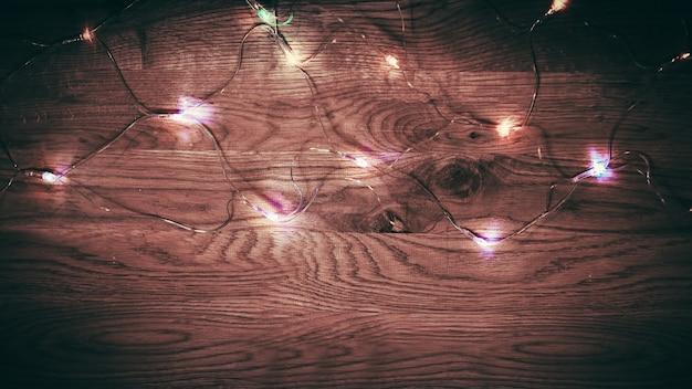 Lumières de noël sur fond de bois avec ombrage sur les bords