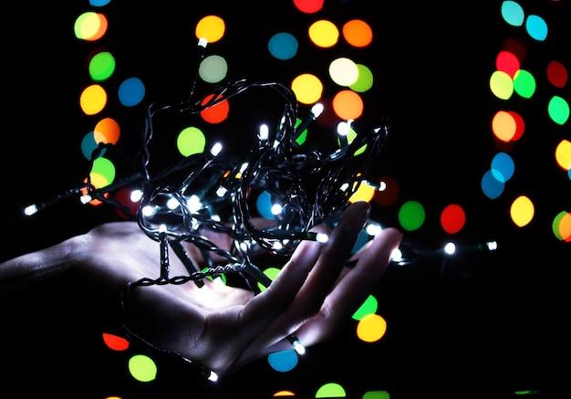 Lumières de noël à la main sur les lumières floues