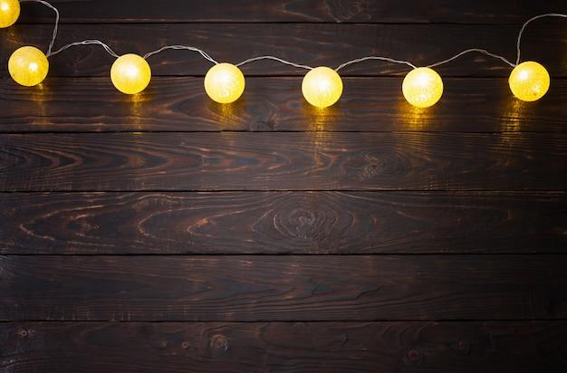 Lumières d'or de noël sur fond de bois foncé