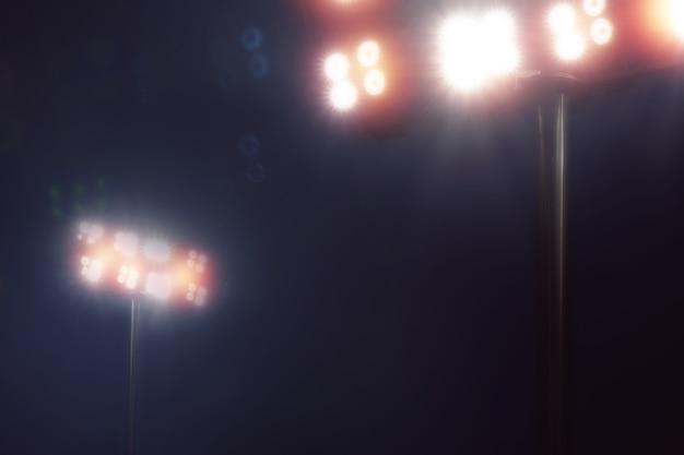 Lumières de stade dans le jeu de sport sur fond de ciel de nuit noire