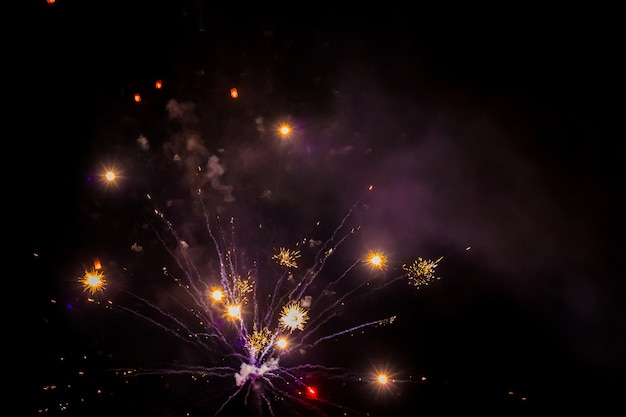 Lumières vives de feux d'artifice festifs dans le ciel nocturne. réveillon de nouvel an