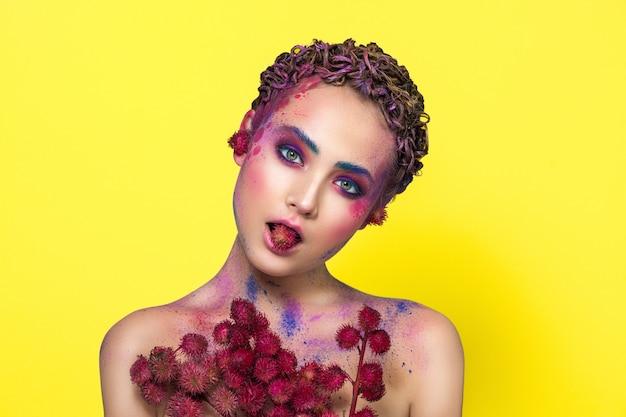 Lumineux jeune mannequin posant avec des fleurs