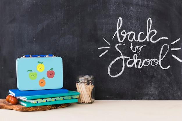 Lunchbox près des cahiers et des crayons