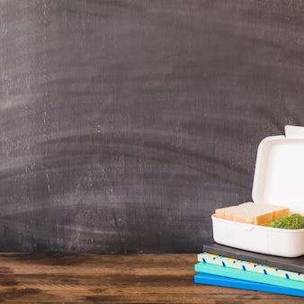 Lunchbox sur tas de cahiers