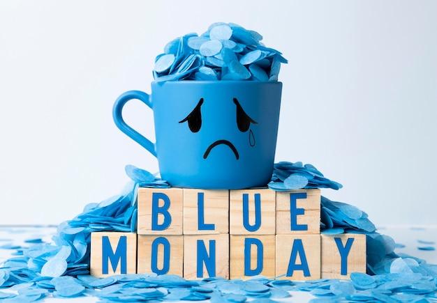 Lundi bleu avec des cubes en bois et une tasse qui pleure