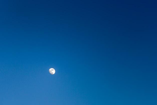 Lune brillamment éclairée dans un ciel bleu foncé sans nuages, nature, paysage