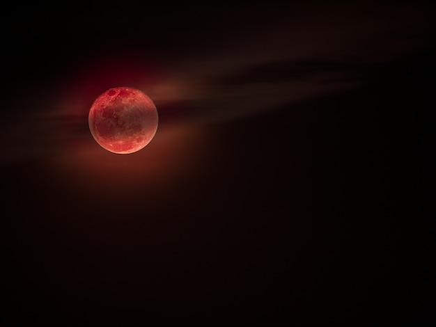 Lune de sang ou lune rouge avec des nuages sur le ciel sombre