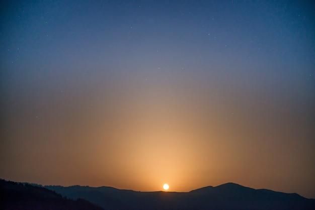 Lune se levant sur le ciel nocturne avec de nombreuses étoiles au-dessus de la chaîne de montagnes