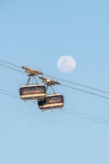 La lune et le téléphérique du pain de sucre à rio de janeiro, brésil - 20 août 2021 : la lune et le téléphérique du pain de sucre dans un beau ciel bleu à rio de janeiro.
