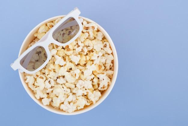 Lunettes 3d se trouvent sur une tasse de pop-corn isolé sur un fond bleu pastel. concept de cinéma. mise à plat.