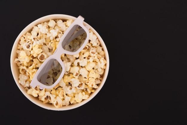 Lunettes 3d se trouvent sur une tasse de pop-corn isolé sur fond noir. concept de cinéma. mise à plat