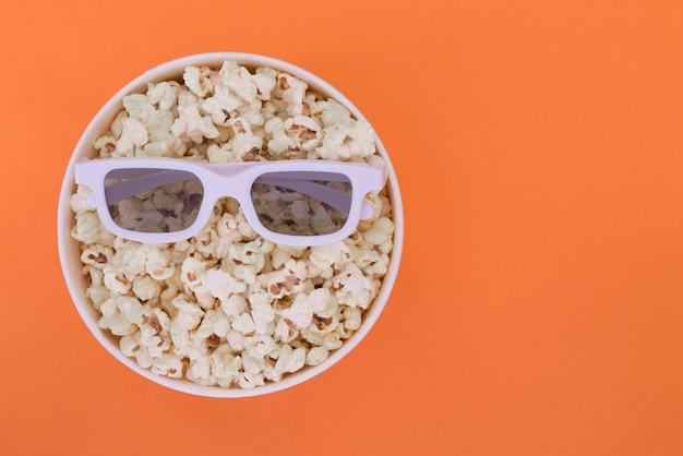 Lunettes 3d se trouvent sur une tasse de pop-corn isolé sur fond orange. concept de cinéma.