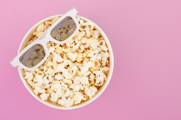Lunettes 3d se trouvent sur une tasse de pop-corn isolé sur un fond rose pastel. concept de cinéma.