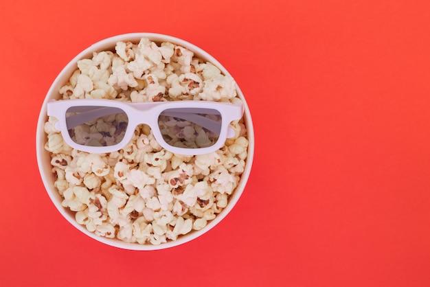 Lunettes 3d se trouvent sur une tasse de pop-corn isolé sur fond rouge. concept de cinéma.