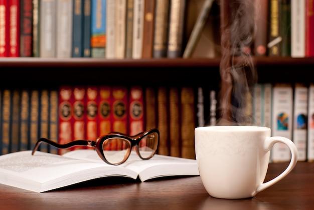 Lunettes allongées sur le livre ouvert et une tasse de thé