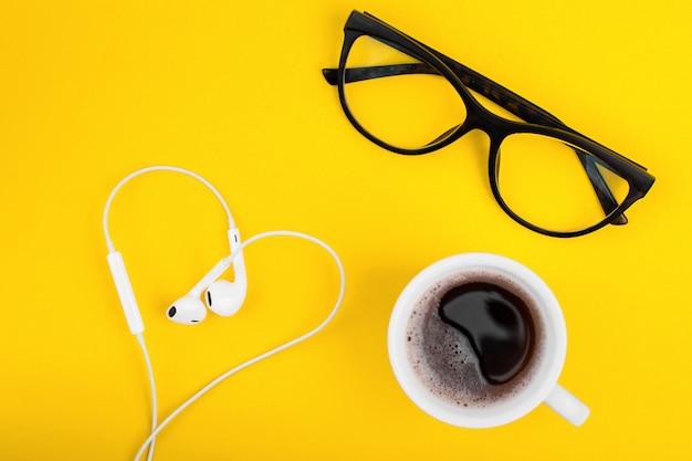 Lunettes, café et écouteurs en forme de coeur sur le bureau jaune.