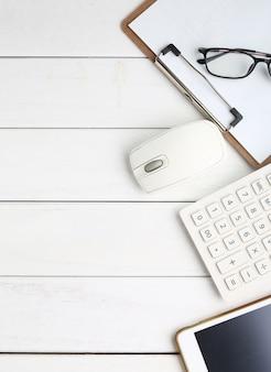 Lunettes, calculatrice et tablette sur bureau blanc et soigné