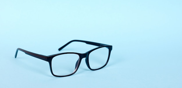 Lunettes classiques noires, sans lunettes de contact de médecine. isolé sur fond bleu. copiez l'espace.