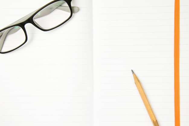 Lunettes et crayon brun sur le cahier de travail. vue de dessus, concept plat laïque.