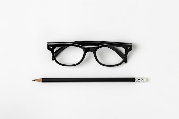 Lunettes et un crayon noir sur fond blanc