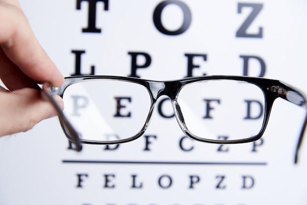 Des lunettes dans les mains sur le fond de la table pour la vision.