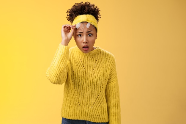 Les lunettes de décollage de la mâchoire d'une étudiante afro-américaine étonnée et sans voix s'écarquillent les yeux surpris ont été abandonnés, regardent quelque chose d'incroyable, debout interrogé frustré, fond jaune.