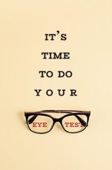 Lunettes élégantes avec le texte flou il est temps de faire votre test de la vue. magasin d'optique, sélection de lunettes, test de la vue, examen de la vue chez l'opticien, concept d'accessoires de mode. vue de dessus, pose à plat