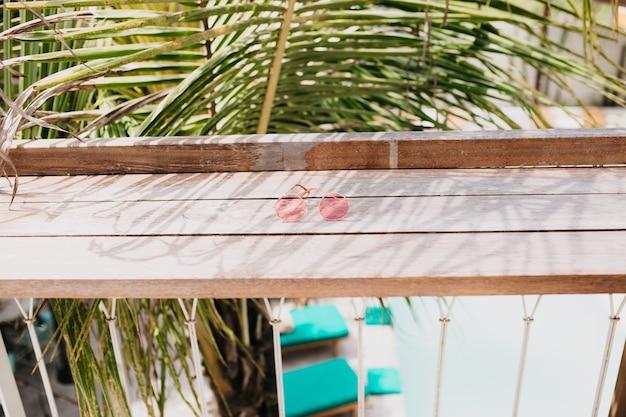 Lunettes féminines élégantes allongées sur une table en bois.