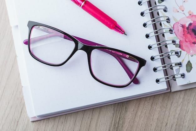 Lunettes de femme avec agenda et crayons